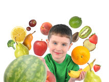 Healthy Fruit Child on White. A boy is holding a banana and apple with a variety of fruit food around the child. There is a white isolated background for a diet Royalty Free Stock Photos