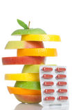 Healthy Fruit plus capsules. A stack of different fruits and some capsules isolated on a white backgorund royalty free stock photography