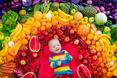 Healthy fruit and vegetable nutrition for kids. Baby boy with variety of fruit and vegetable. Colorful rainbow of raw fresh fruits and vegetables. Child eating Stock Images