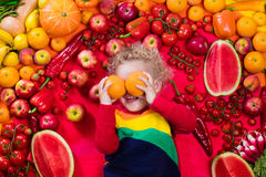Healthy fruit and vegetable nutrition for kids. Baby boy with variety of fruit and vegetable. Colorful rainbow of raw fresh fruits and vegetables. Child eating Royalty Free Stock Images