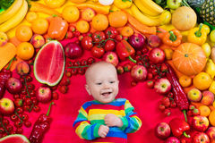 Healthy fruit and vegetable nutrition for kids. Baby boy with variety of fruit and vegetable. Colorful rainbow of raw fresh fruits and vegetables. Child eating Royalty Free Stock Photo