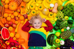 Healthy fruit and vegetable nutrition for kids. Baby boy with variety of fruit and vegetable. Colorful rainbow of raw fresh fruits and vegetables. Child eating Stock Photos