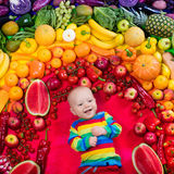 Healthy fruit and vegetable nutrition for kids. Baby boy with variety of fruit and vegetable. Colorful rainbow of raw fresh fruits and vegetables. Child eating Stock Photo