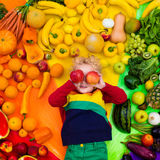 Healthy fruit and vegetable nutrition for kids. Baby boy with variety of fruit and vegetable. Colorful rainbow of raw fresh fruits and vegetables. Child eating Stock Image