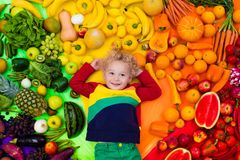 Healthy fruit and vegetable nutrition for kids. Baby boy with variety of fruit and vegetable. Colorful rainbow of raw fresh fruits and vegetables. Child eating Royalty Free Stock Photography