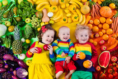 Healthy fruit and vegetable nutrition for kids. Boy, girl and baby with variety of fruit and vegetable. Colorful rainbow of raw fruits and vegetables. Child Royalty Free Stock Photography