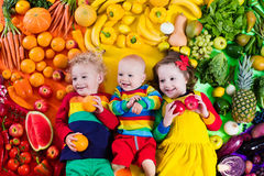Healthy fruit and vegetable nutrition for kids. Boy, girl and baby with variety of fruit and vegetable. Colorful rainbow of raw fruits and vegetables. Child Stock Photo
