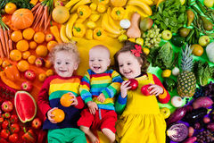 Healthy fruit and vegetable nutrition for kids. Boy, girl and baby with variety of fruit and vegetable. Colorful rainbow of raw fruits and vegetables. Child Stock Images