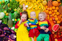 Healthy fruit and vegetable nutrition for kids. Boy, girl and baby with variety of fruit and vegetable. Colorful rainbow of raw fruits and vegetables. Child Royalty Free Stock Image