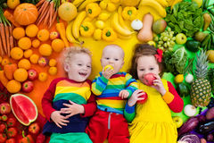 Healthy fruit and vegetable nutrition for kids. Boy, girl and baby with variety of fruit and vegetable. Colorful rainbow of raw fruits and vegetables. Child Royalty Free Stock Photos