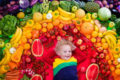 Healthy fruit and vegetable nutrition for kids. Little boy with variety of fruit and vegetable. Colorful rainbow of raw fresh fruits and vegetables. Child eating Royalty Free Stock Photography