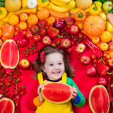 Healthy fruit and vegetable nutrition for kids. Little girl with variety of fruit and vegetable. Colorful rainbow of raw fresh fruits and vegetables. Child Stock Images
