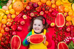 Healthy fruit and vegetable nutrition for kids. Little girl with variety of fruit and vegetable. Colorful rainbow of raw fresh fruits and vegetables. Child Stock Photography