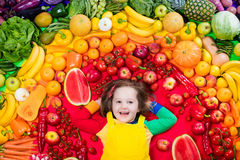 Healthy fruit and vegetable nutrition for kids. Little girl with variety of fruit and vegetable. Colorful rainbow of raw fresh fruits and vegetables. Child Stock Photos