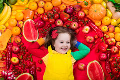 Healthy fruit and vegetable nutrition for kids. Little girl with variety of fruit and vegetable. Colorful rainbow of raw fresh fruits and vegetables. Child Royalty Free Stock Photography