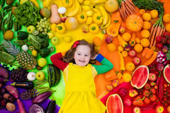 Healthy fruit and vegetable nutrition for kids. Little girl with variety of fruit and vegetable. Colorful rainbow of raw fresh fruits and vegetables. Child Royalty Free Stock Photos
