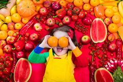 Healthy fruit and vegetable nutrition for kids. Little girl with variety of fruit and vegetable. Colorful rainbow of raw fresh fruits and vegetables. Child Royalty Free Stock Image