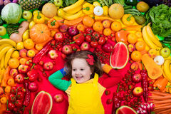 Healthy fruit and vegetable nutrition for kids. Little girl with variety of fruit and vegetable. Colorful rainbow of raw fresh fruits and vegetables. Child Stock Photo
