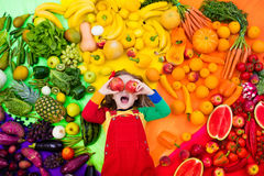 Healthy fruit and vegetable nutrition for kids. Little girl with variety of fruit and vegetable. Colorful rainbow of raw fresh fruits and vegetables. Child Royalty Free Stock Images
