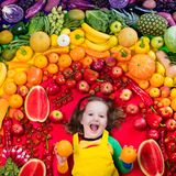 Healthy fruit and vegetable nutrition for kids. Little girl with variety of fruit and vegetable. Colorful rainbow of raw fresh fruits and vegetables. Child Royalty Free Stock Photo