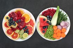 Healthy Fruit and Vegetable Super Food. Health fresh fruit and vegetables on plates on slate background with super foods high in dietary fibre, antioxidants royalty free stock images