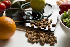 Healthy fruit,vegetables and stethoscope on scales. Weight loss and right nutrition concept.  royalty free stock photos