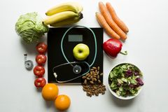 Healthy fruit,vegetables and stethoscope on scales. Weight loss and right nutrition concept.  royalty free stock images