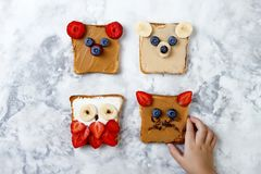 Healthy funny face sandwiches for kids. Animal faces toast with peanut and cashew butter, ricotta, banana, strawberry. Healthy funny face sandwiches for kids stock photo