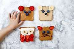 Healthy funny face sandwiches for kids. Animal faces toast with peanut and cashew butter, ricotta, banana, strawberry. Healthy funny face sandwiches for kids royalty free stock photos