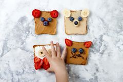 Healthy funny face sandwiches for kids. Animal faces toast with peanut and cashew butter, ricotta, banana, strawberry. Healthy funny face sandwiches for kids royalty free stock image