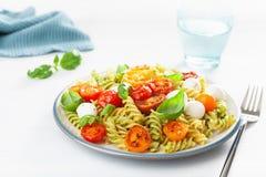 Healthy fusilli pasta with pesto sauce, roasted tomatoes, mozzarella royalty free stock images