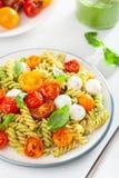 Healthy fusilli pasta with pesto sauce, roasted tomatoes, mozzarella stock images