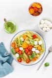 Healthy fusilli pasta with pesto sauce, roasted tomatoes, mozzarella royalty free stock image