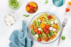Healthy fusilli pasta with pesto sauce, roasted tomatoes, mozzarella stock photos