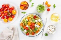 Healthy fusilli pasta with pesto sauce, roasted tomatoes, mozzarella stock photo