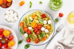 Healthy fusilli pasta with pesto sauce, roasted tomatoes, mozzarella stock image