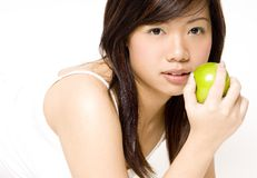 Healthy Girl 4. A pretty young asian woman in white eating an apple Stock Photography