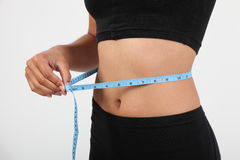 Healthy girl checking waist size with tape measure Royalty Free Stock Images
