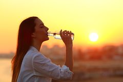 Healthy girl drinking water at sunset. Side view backlight portrait of a healthy girl drinking water at sunset Stock Image