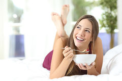Healthy girl eating cereals at breakfast. Lying on the bed at home or hotel Stock Images
