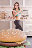 Healthy girl fighting against hamburger Stock Images