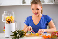 Healthy girl making fruits smoothies Royalty Free Stock Images