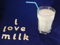 Healthy glass of milk. A healthy glass of cold fresh milk  with a blue straw ,set with a blue background with words saying I love milk Royalty Free Stock Images