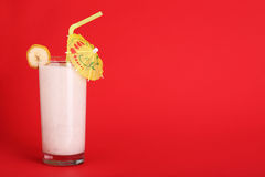 Healthy glass of smoothies banana flavor on red Royalty Free Stock Image