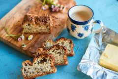 Healthy gluten-free bread with seeds. Healthy breakfast with gluten -free bread with seeds, butter and cup of drink on wooden kitchen board and blue table royalty free stock photo