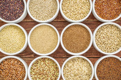 Healthy, gluten free grains abstract. (quinoa, brown rice, millet, amaranth, teff, buckwheat, sorghum), top view of small round bowls against rustic wood Royalty Free Stock Photos