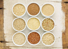 Healthy, gluten free grains abstract. (quinoa, brown rice, millet, amaranth, teff, buckwheat, sorghum), top view of small round bowls against rustic barn wood Stock Photos