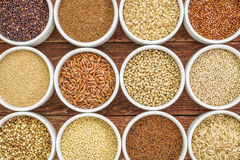 Healthy, gluten free grains abstract. (quinoa, brown rice, millet, amaranth, teff, buckwheat, sorghum), top view of small round bowls against rustic wood Royalty Free Stock Image