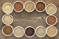Healthy, gluten free grains collection. (quinoa, brown rice, millet, amaranth, teff, buckwheat, sorghum) , top view of small round bowls against rustic wood Royalty Free Stock Photo