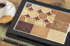 Healthy gluten free grains on tablet. Reviewing pictures of healthy gluten free grains (quinoa, kaniwa, brown rice, millet, amaranth, teff, buckwheat, sorghum) Stock Photo